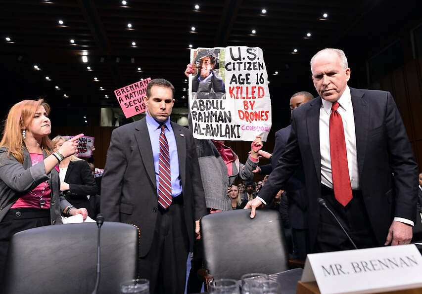 Anti-war protesters shout slogans as John Brennan (R), President Barack Obama's pick to lead the CIA