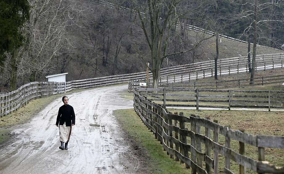 In this photo made on Tuesday, Jan. 29, 2013, a young Amish woman walks down the dirt road between the farms in Bergholz, Ohio that are worked by the families of sixteen men and women facing sentencing Friday, Feb. 8, 2013 in beard-cutting attacks on fellow Amish in Ohio. The defendants want leniency so they can return to their homes and farms, to teach their sons a trade and their daughters how to sew, cook and keep house.  Photo: Keith Srakocic, Associated Press