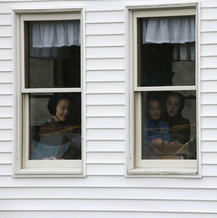 Amish children look out the windows of the home of Sam Mullet Sr., who faces sentencing in Ohio beard-cutting attacks. Photo: Keith Srakocic, Associated Press