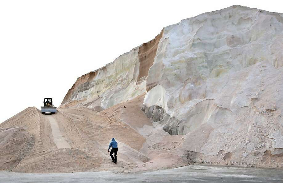 A worker walks up towards a plow smoothing a large salt pile at Eastern Salt Company in Chelsea, Mas