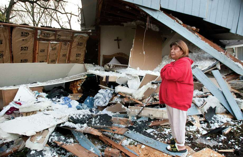 Dora Estrada, 62, looks at the remains of her bedroom after a driver crashed into the front of her home while she was sleeping early Thursday morning. The driver was leading police on a chase when he apparently lost control of the pickup and rammed into the house. Photo: Cody Duty, Staff / © 2013 Houston Chronicle
