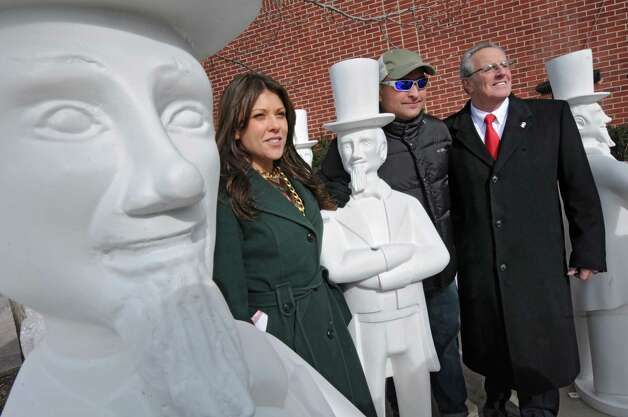 From left, Troy BID Director Elizabeth Young, artist John Bulmer of Halfmoon and Troy Mayor Lou Rosamilia stand next to twenty-one Uncle Sam statues that were delivered and briefly lined up on the River Street on Thursday Feb. 7, 2013 in Troy, N.Y. (Lori Van Buren / Times Union) Photo: Lori Van Buren