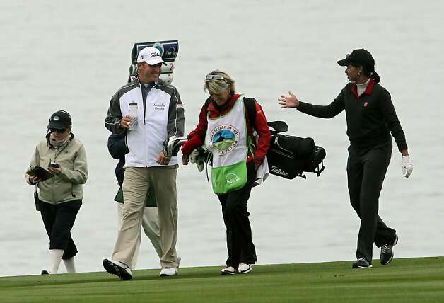 Condoleezza Rice (right) talks with pro partner Jason Bohn as they walk up the 8th fairway in the first round at Pebble Beach. Photo: Lance Iversen, The Chronicle