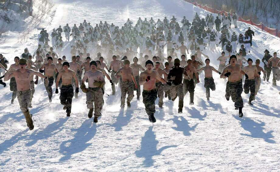 Shirtless South Korean Marines and their U.S. counterparts from 3-Marine Expeditionary Force 1st Battalion from Kaneho Bay, Hawaii, run on a snow covered field during their Feb. 4-22 joint military winter exercise in Pyeongchang, east of Seoul, South Korea, Thursday, Feb. 7, 2013. More than 400 marines from the two countries participated in the joint winter exercise held for the first time in South Koreas. Photo: Lee Jin-man, Associated Press / AP