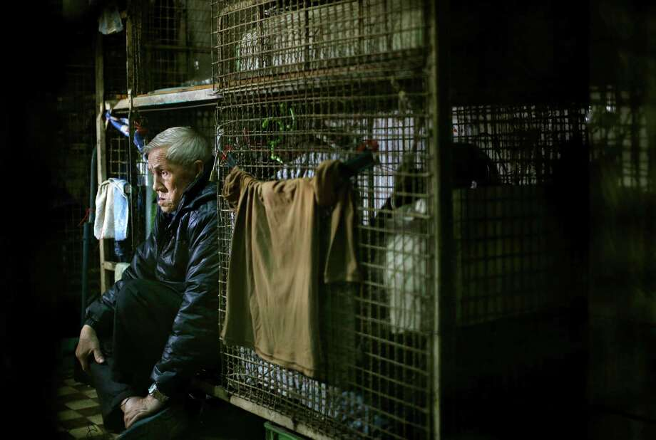In this Jan. 25, 2013 photo, 77-year-old Yeung Ying Biu sits inside his 1.5 square meter (16 square feet) cage, which he calls home, in Hong Kong. For many of the richest people in Hong Kong, one of Asia's wealthiest cities, home is a mansion with an expansive view from the heights of Victoria Peak. For some of the poorest, home is a metal cage. Some 100,000 people in the former British colony live in what's known as inadequate housing, according to the Society for Community Organization, a social welfare group.  (AP Photo/Vincent Yu) Photo: Vincent Yu