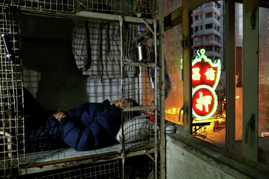In this Jan. 25, 2013 photo, 62-year-old Cheng Man Wai lays in his cage, measuring 1.5 square meters (16 square feet),  which he calls home, in Hong Kong. For many of the richest people in Hong Kong, one of Asia's wealthiest cities, home is a mansion with an expansive view from the heights of Victoria Peak. For some of the poorest, home is a metal cage. Some 100,000 people in the former British colony live in what's known as inadequate housing, according to the Society for Community Organization, a social welfare group.   (AP Photo/Vincent Yu) Photo: Vincent Yu