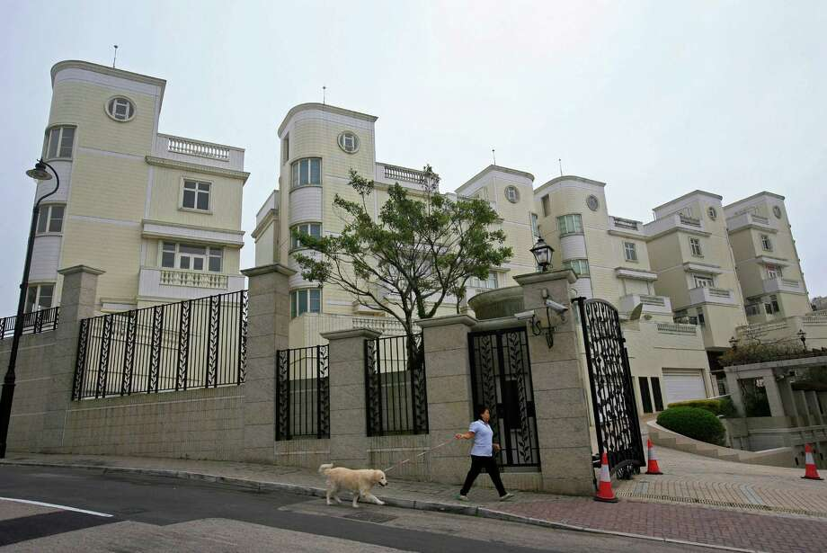 A maid walks a dog outside luxury houses on Victoria Peak, Hong Kong's most exclusive neighborhood, Thursday, Feb. 7, 2013. For many of the richest people in Hong Kong, one of Asia's wealthiest cities, home is a mansion with an expansive view from the heights of Victoria Peak. For some of the poorest, home is a metal cage. Some 100,000 people in the former British colony live in what's known as inadequate housing, according to the Society for Community Organization, a social welfare group.   (AP Photo/Vincent Yu) Photo: Vincent Yu