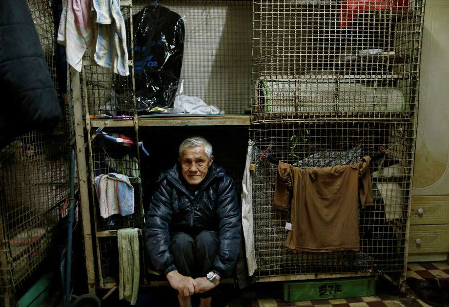 In this Jan. 25, 2013 photo, 77-year-old Yeung Ying Biu sits partially inside the cage, measuring 1.5 square meters (16 square feet),  which he calls home, in Hong Kong.  For many of the richest people in Hong Kong, one of Asia's wealthiest cities, home is a mansion with an expansive view from the heights of Victoria Peak. For some of the poorest, home is a metal cage. Some 100,000 people in the former British colony live in what's known as inadequate housing, according to the Society for Community Organization, a social welfare group. (AP Photo/Vincent Yu) Photo: Vincent Yu