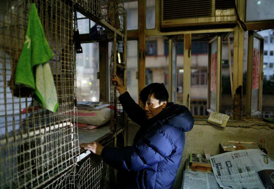 In this Jan. 25, 2013 photo, 62-year-old Cheng Man Wai climbs up to the 1.5 square meter (16 square feet) cage he calls home, in Hong Kong. For many of the richest people in Hong Kong, one of Asia's wealthiest cities, home is a mansion with an expansive view from the heights of Victoria Peak. For some of the poorest, home is a metal cage. Some 100,000 people in the former British colony live in what's known as inadequate housing, according to the Society for Community Organization, a social welfare group.  (AP Photo/Vincent Yu) Photo: Vincent Yu