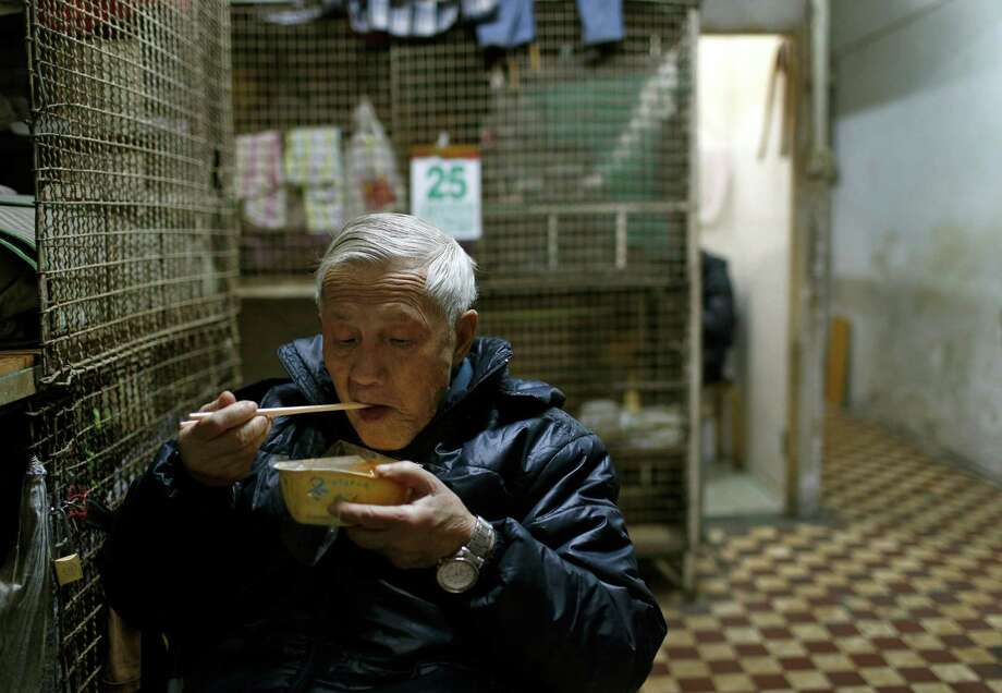 In this Jan. 25, 2013 photo, 77-year-old Yeung Ying Biu eats next to the cage, measuring 1.5 square meters (16 square feet), he calls home, in Hong Kong.  For many of the richest people in Hong Kong, one of Asia's wealthiest cities, home is a mansion with an expansive view from the heights of Victoria Peak. For some of the poorest, home is a metal cage. Some 100,000 people in the former British colony live in what's known as inadequate housing, according to the Society for Community Organization, a social welfare group. (AP Photo/Vincent Yu) Photo: Vincent Yu