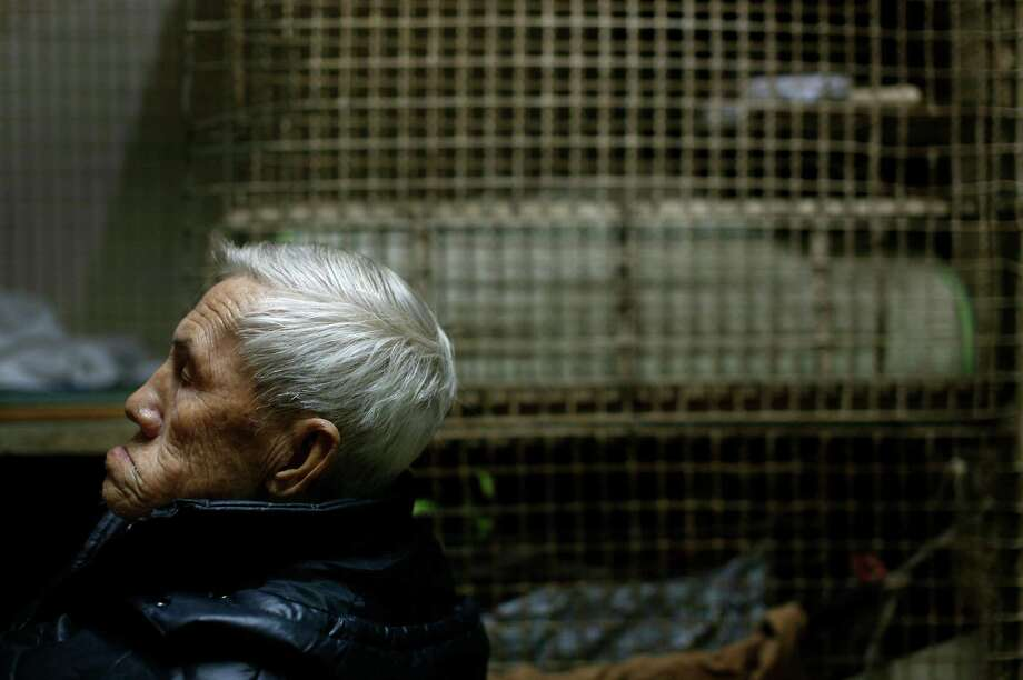 In this Jan. 25, 2013 photo, 77-year-old Yeung Ying Biu sits next to the cage, measuring 1.5 square meters (16 square feet), he calls home, in Hong Kong.  For many of the richest people in Hong Kong, one of Asia's wealthiest cities, home is a mansion with an expansive view from the heights of Victoria Peak. For some of the poorest, home is a metal cage. Some 100,000 people in the former British colony live in what's known as inadequate housing, according to the Society for Community Organization, a social welfare group. (AP Photo/Vincent Yu) Photo: Vincent Yu