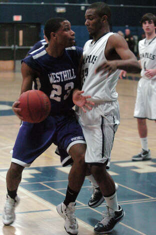 Westhill's Ariel DelCruz and Staples' Darryl Wiggins, right, in action as Staples High School hosts Westhill in a boys basketball game in Westport, Conn., Feb. 7, 2013. Photo: Keelin Daly / Keelin Daly