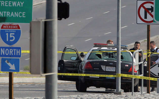 Los Angeles Police Department officers investigate the site of a shooting Thursday. Christopher Dorner is suspected of this shooting of two LAPD officers. Photo: Nick Ut, STF / AP