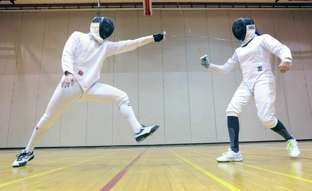 Greenwich High School fencers, Harrison Tune, left, a junior, and Ava Salzer, a senior, during fencing practice at Greenwich High School, Thursday night, Feb. 7, 2013. Photo: Bob Luckey / Greenwich Time