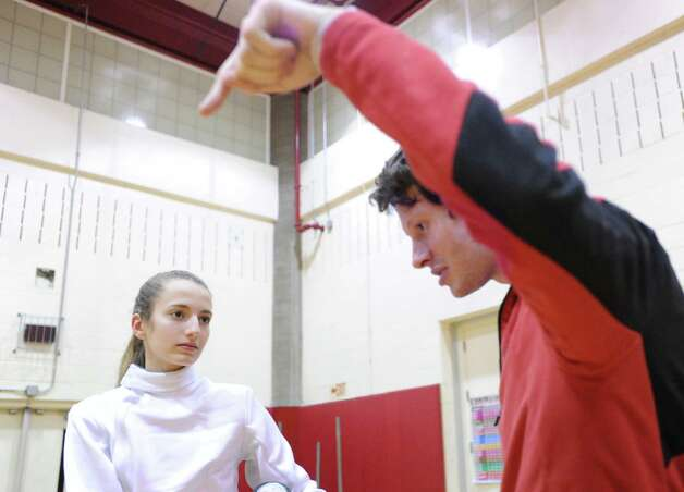 At left, Greenwich High School fencer Juliette McGinnis, 15, a sophomore, listens to her coach, Donald Grunewald, give instruction during fencing practice at Greenwich High School, Thursday night, Feb. 7, 2013. Photo: Bob Luckey / Greenwich Time