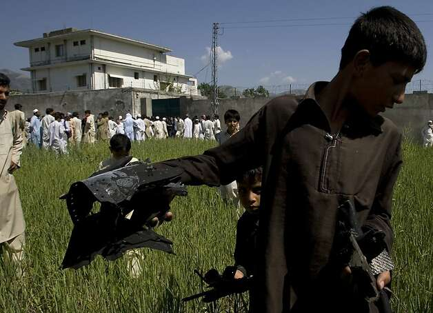 A Pakistani youngster shows metal pieces collected from wheat field outside a house, seen background, where al-Qaida leader Osama bin Laden lived in Abbottabad, Pakistan, on Tuesday, May 3, 2011.  Local residents showed off small parts of what appeared to be a U.S. helicopter that Washington said malfunctioned and was disabled by the American commando strike team as they retreated. Photo: Anjum Naveed, AP