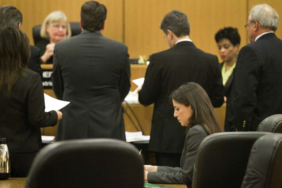Behind a phalanx of attorneys, Rachel Brown reads court papers Thursday during a hearing before state District Judge Sheri Dean. Her ex-husband was absent. Photo: Brett Coomer, Houston Chronicle / © 2013 Houston Chronicle