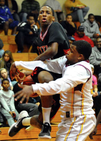 St. Joseph's #35 Erick Langston fouls Central's #10 ShaQuan Bretoux as he attempts a shot, during boys basketball action in Trumbull, Conn. on Thursday February 7, 2013. Photo: Christian Abraham / Connecticut Post