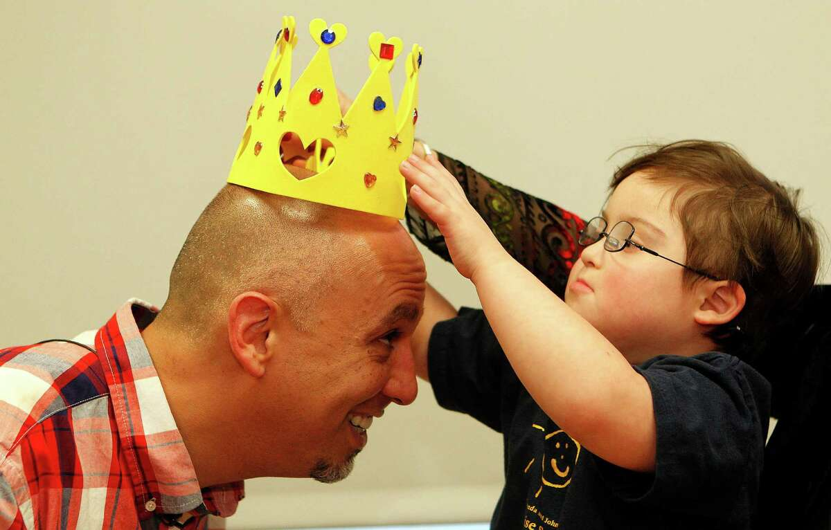 Waiter, Michael Garcia has a crown placed on his head by his new friend, 5-year-old Milo Castillo, after students and teachers from The Rise School of Houston honored Garcia for standing up for their classmate Milo Wednesday, Feb. 6, 2013, in Houston. Michael Garcia, a waiter at Laurenzo's, refused to serve a couple who make a rude remark about Milo being a special needs child.