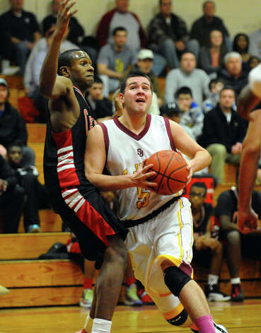St. Joseph's #5 Jon Dzurenda tries to drive past Central's #12 Ricky Grant on his way to the net, during boys basketball action in Trumbull, Conn. on Thursday February 7, 2013. Photo: Christian Abraham / Connecticut Post