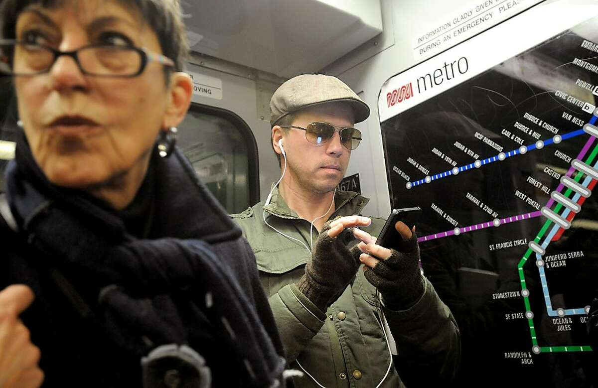 Peter Campbell checks his phone while riding Muni on Thursday, Feb. 7, 2013, in San Francisco.