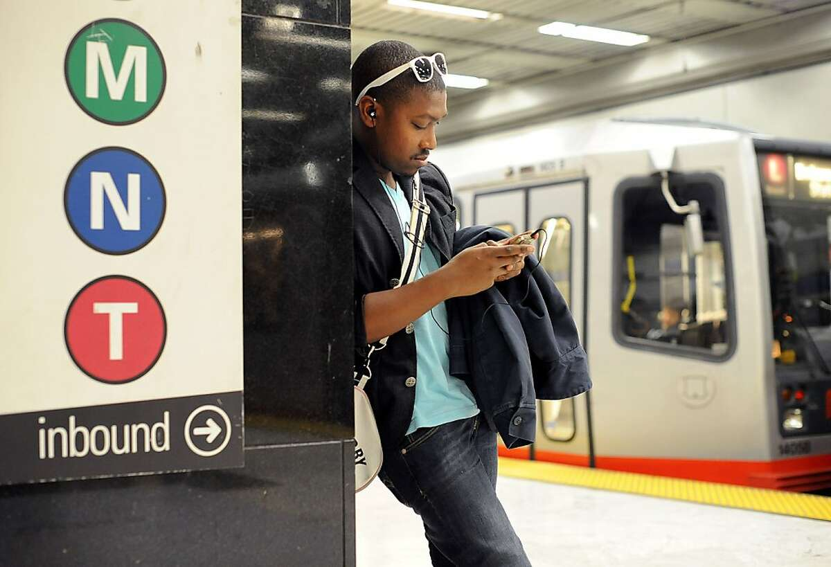 Aaron Groner checks his phone while waiting for a Muni streetcar on Thursday, Feb. 7, 2013, in San Francisco.