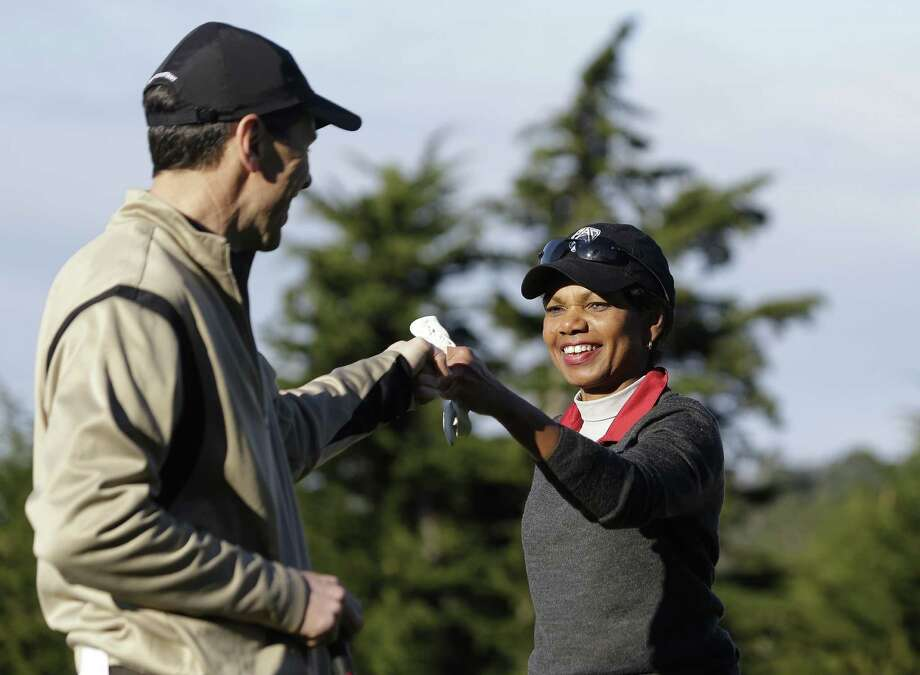 Former Secretary of State Condoleezza Rice is greeted by Randall Stephenson after making a par putt on the second hole Thursday at Pebble Beach. Hunter Mahan and Russell Knox share the individual lead. Photo: Eric Risberg / Associated Press