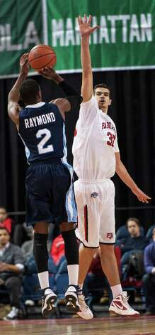 Fairfield University's Josip Mikulic tries to block a shot by St. Peter's University's Yvon Raymond on during a men's basketball game played at the Webster Bank Arena, Bridgeport, CT on Thursday February 7th, 2013. Photo: Mark Conrad / Connecticut Post Freelance