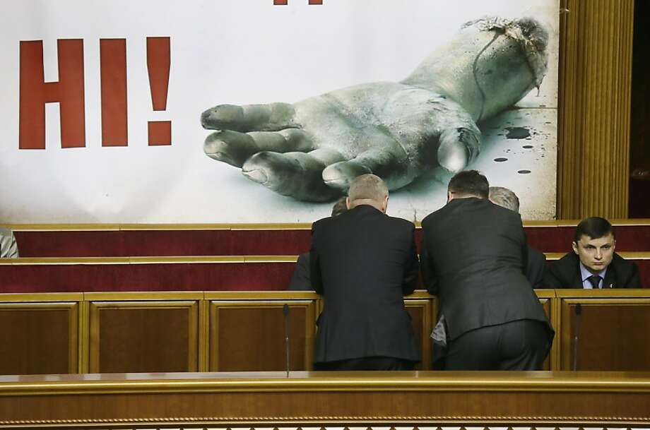 Ukrainian lawmakers talks in the parliament session hall in Kiev, Ukraine, Thursday, Feb. 7, 2013. The severed hand and 'No' on a poster  is supposed to symbolize opposition's call to stop corruption in parliament.  Opposition lawmakers block the work of the Ukrainian parliament  in a sign of protest against corruption. Photo: Efrem Lukatsky, Associated Press