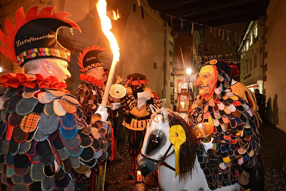 "A group of the Constance fool's guild ""Blätzlebueben"" with lanterns and torches is pictured in Constance, southern Germany, on February 7 , 2013. Since the early morning, hundreds of dressed up people walk through the city to wake the population.  Photo: Felix Kaestle, AFP/Getty Images"