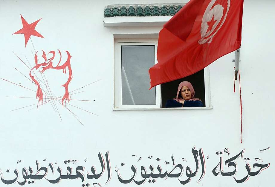 A Tunisian woman watches behind a national flag as mourners pour into Jebel Jelloud, a suburb of Tunis and hometown of assassinated leftist leader Chokri Belaid, on February 7, 2013 at a branch of the Party of Democratic Patriots (Arabic writing) which he headed. Police was deployed in force in Tunis amid fears the murder of the 48-year-old opposition figure could reignite nationwide violence, as the ruling Islamists broke ranks over how to defuse the crisis. Belaid's family said his funeral will take place on February 8 after the main weekly prayers.  Photo: Fethi Belaid, AFP/Getty Images