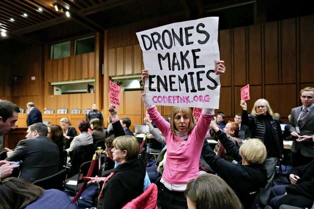 Protesters from CODEPINK, a group opposed to U.S. militarism, including co-founder Medea Benjamin, center, disrupt the start of the Senate Intelligence Committee confirmation hearing for John Brennan, Thursday, Feb. 7, 2013, on Capitol Hill in Washington. (AP Photo/J. Scott Applewhite) Photo: J. Scott Applewhite