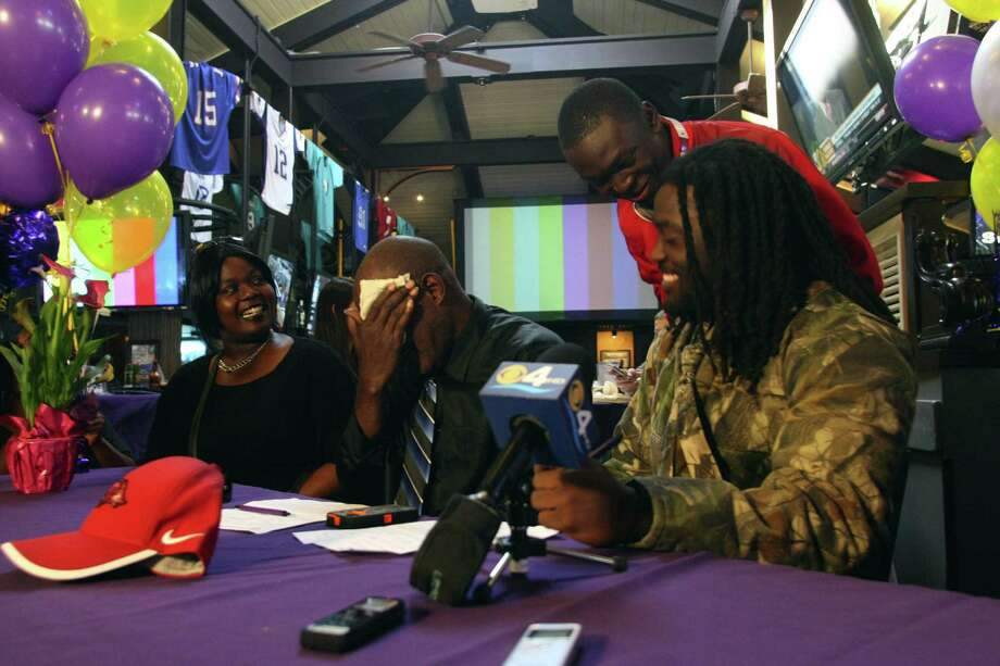 Alex Collins (right), a star high school running back in Florida, sits down with his aunt, Loretta Collins (left), and his father, Johnny Collins, to sign his national letter of intent with Arkansas. Photo: Mike Stocker / South Florida Sun Sentinel