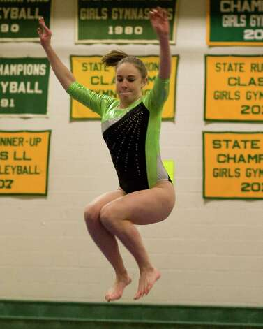 New Milford's Erica Davidson competes on the balance beam during the SWC Gymnastics Championships Thursday night at New Milford High School. Photo: Barry Horn