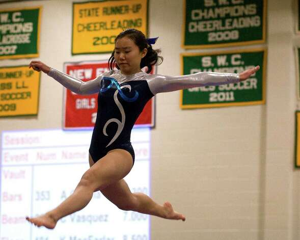 Newtown's Daisy Zheng competes on the balance beam at the SWC Gymnastics Championships Thursday night at New Milford High School. Photo: Barry Horn