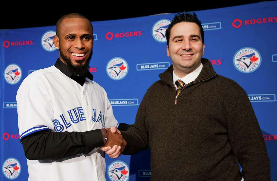 ADVANCE FOR WEEKEND EDITIONS, FEB. 9-10 - FILE - In this Jan. 17, 2013, file photo, Toronto Blue Jay new shortstop Jose Reyes, left, shakes hands with general manager Alex Anthopoulos during a baseball news conference in Toronto. rom Joker Marchant Stadium in Lakeland, Fla., to HoHoKam Park in Mesa, Ariz., bats and balls will be broken out next week when teams start reporting for spring training. (AP Photo/The Canadian Press, Aaron Vincent Elkaim, File) Photo: Aaron Vincent Elkaim