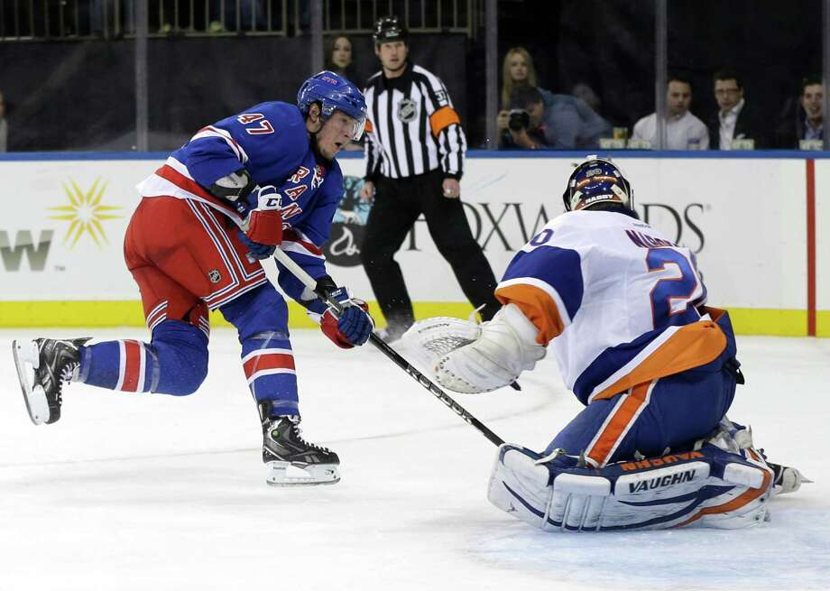 New York Rangers' J.T. Miller, left, scores a goal past New York Islanders goalie Evgeni Nabokov, right, during the second period of the NHL hockey game in New York, Thursday, Feb. 7, 2013.  (AP Photo/Seth Wenig) Photo: Seth Wenig
