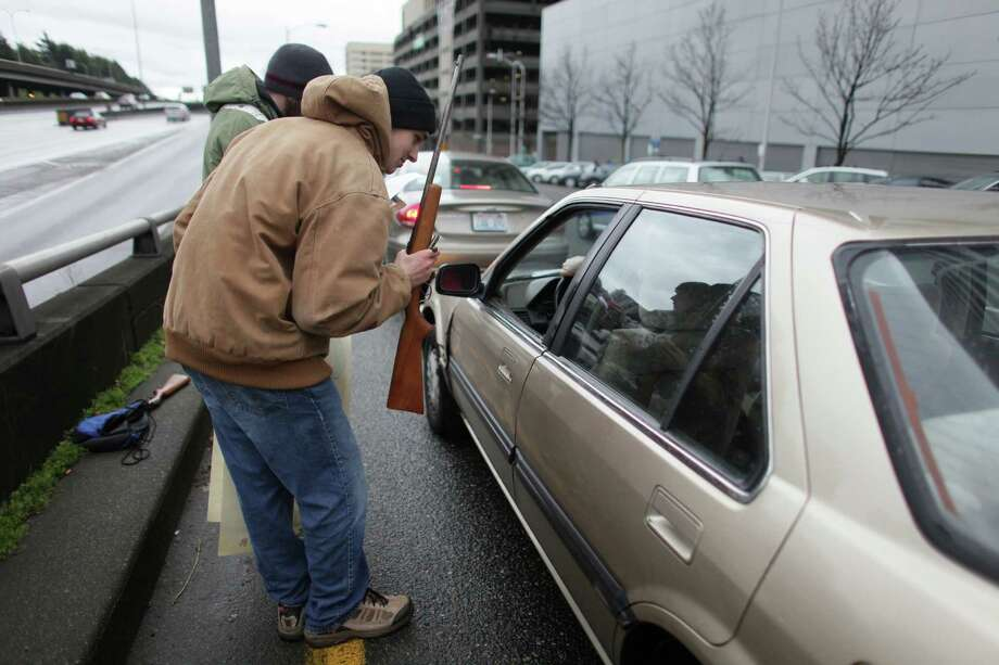 Thomas Craft, 15, purchases a gun from a man in a car along with Patrick Sprinker, 20, rear, as people wait in line to exchange firearms for gift cards during the city of Seattle's gun buyback program on Saturday, Jan. 26, 2013. The gun exchange program brought out people looking for deals on firearms, including Craft. The purchase of the firearms by Craft and Sprinker was completely legal. Photo: JOSHUA TRUJILLO, SEATTLEPI.COM / SEATTLEPI.COM