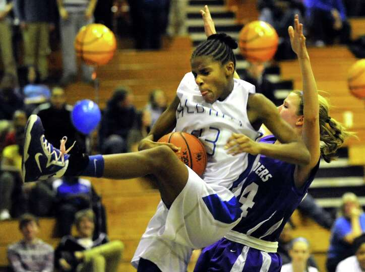 Albany's Mylah Chandler (23), center, wins the rebound over Catholic Central's Madison Purcell (24)