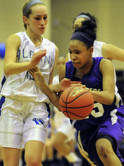 Catholic Central's Alliyah Gillespie (15), right, drives past Albany's Kelsey Green (12) during thei