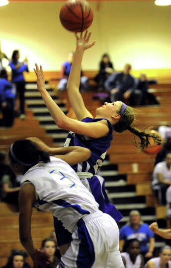 Catholic Central's Madison Purcell (24), right, shoots for the hoop and gets a foul from Albany's Ay