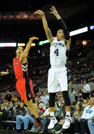 Danny Green of the San Antonio Spurs scores on a three-point attempt as Landry Fields of the Toronto Raptors defends during NBA action at the AT&T Center on Wednesday, Dec. 26, 2012. Photo: Billy Calzada, San Antonio Express-News / SAN ANTONIO EXPRESS-NEWS