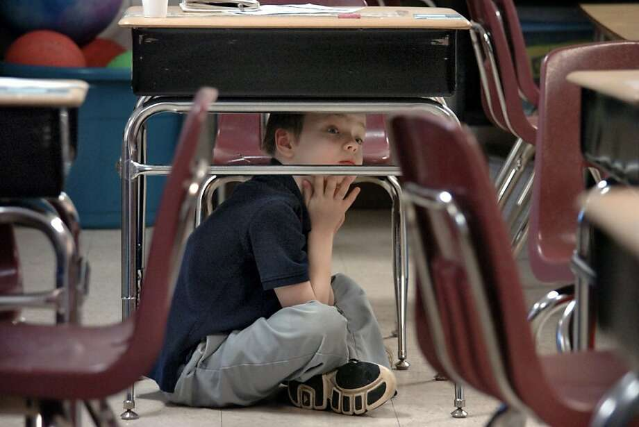 Anthony Hale lifts his head to look around as he and other students in Cheryl Logan's second-grade classroom at Kendall Elementary School are given the all-clear after the Great Central U.S. ShakeOut earthquake drill in Marion, Ind., on Thursday, Feb. 7, 2013.  Photo: Jeff Morehead, Associated Press