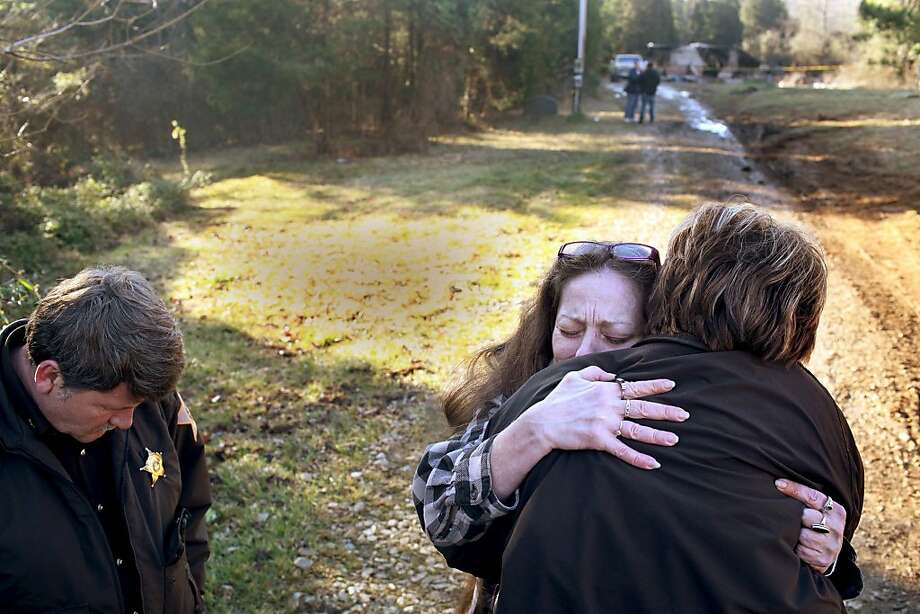 Crawford County, Ind., Sheriff Tim Wilkerson, left, and Deputy Debra Young, back to camera. comfort Rose Turben, center, as they stand in front of a mobile home where five of Turben's family members died in a mobile home fire Thursday, Feb. 7, 2013 in Sulpher, Ind.   Wilkerson said it took firefighters two hours to extinguish the fire that gutted the home, according to the The Courier Journal.  Photo: Aaron Borton, Associated Press