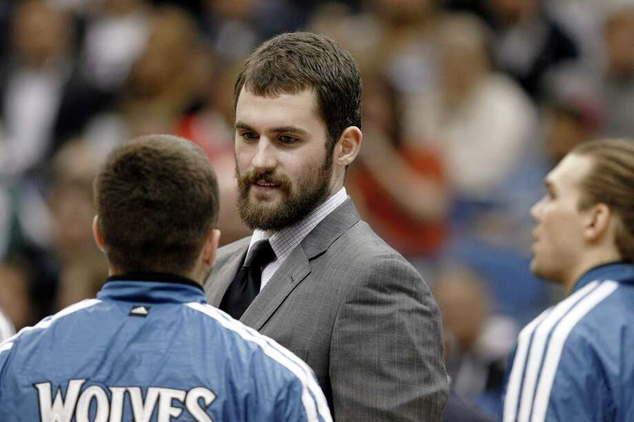Injured Timberwolves forward Kevin Love, talking with teammates during Wednesday's game against the Spurs, hasn't had the season he was hoping for. Photo: Genevieve Ross / Associated Press
