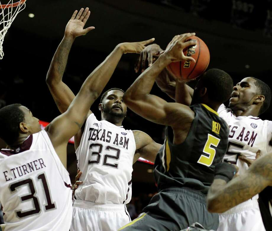 Missouri's Keion Bell (5) finds himself surrounded by Texas A&M defenders Elston Turner (31), Kourtney Roberson (32) and Ray Turner (35) as he goes up for a shot in the second half Thursday night. Photo: Pat Sullivan, STF / AP