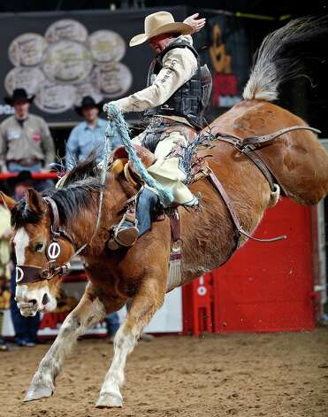 Taos Muncy, of Corona, N.M., competes in the saddle bronc riding event during the San Antonio Stock Show & Rodeo Thursday Feb. 7, 2013 at the AT&T Center. Muncy scored a 83 on the ride. Photo: Edward A. Ornelas, San Antonio Express-News / © 2013 San Antonio Express-News