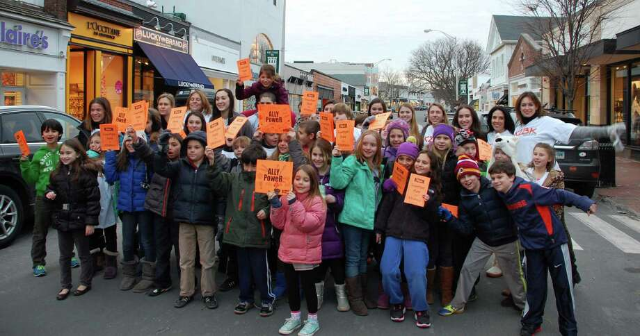 "Staples High School students who take part in the mentoring program, Kool to be Kind, gathered with some of the third-grade students they mentor Thursday on Main Street to promote the ""Westport's Hunt for Kindness"" scavenger hunt.   WESTPORT NEWS, CT 2/7/13 Photo: Jarret Liotta"