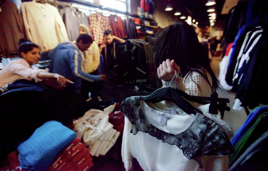 In this Wednesday, Dec. 12, 2012 photo, Lana Nguyen, right, holds clothes to try on as she shops with Lisa George, left, and friends in an H&M store, in Atlanta. The Federal Reserve reports how much consumers borrowed in December on Thursday, Feb. 7, 2013.  (AP Photo/David Goldman) Photo: David Goldman