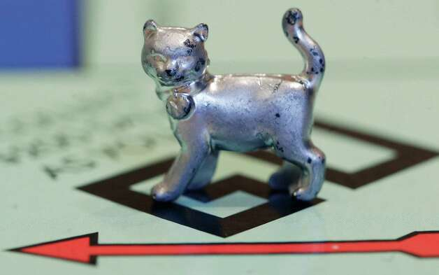 FILE - In this Tuesday, Feb. 5, 2013 file photo, the newest Monopoly token, a cat, rests on the game board at Hasbro Inc. headquarters, in Pawtucket, R.I. Hasbro is reporting their fourth quarter 2012 earnings on Thursday, Feb. 7, 2013. ((AP Photo/Steven Senne, File) Photo: Steven Senne
